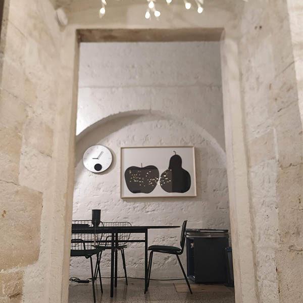 stanza con sedie e quadro di raffigurante una mela e una pera giganti