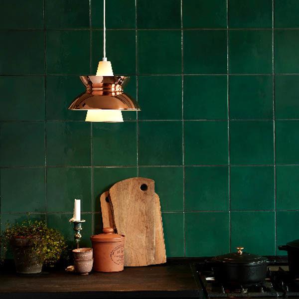 Cucina illuminata da una lampada color rame.